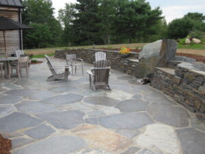 Beautiful slate patio with stone retaining wall that has a built in fire pit with two large granite backing reflector stones.